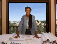 Picture of a smiling female architect standing in front of a desk covered with blueprints. The woman architect has her palms flat down on the piles of blue prints. Behind her is a large window with blue sky showing through.